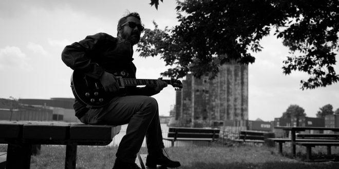 Paul on Bench with guitar