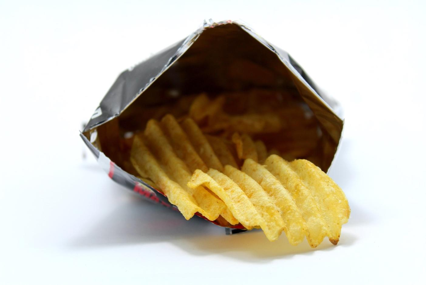 Packet of crisps open with crisp hanging out