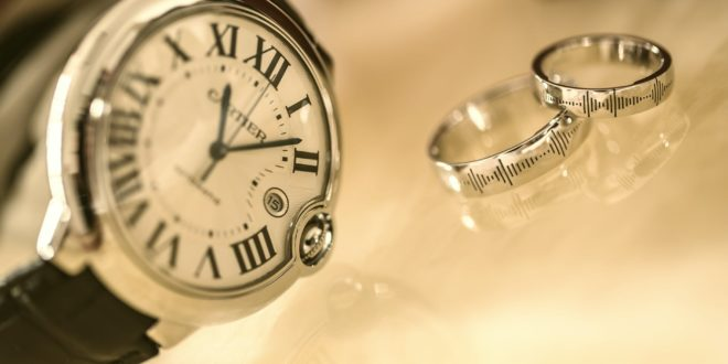silver wedding rings near silver round analog watch