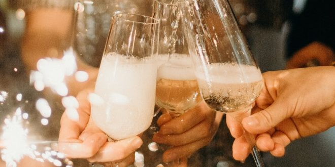 person pouring champagne on champagne flutes