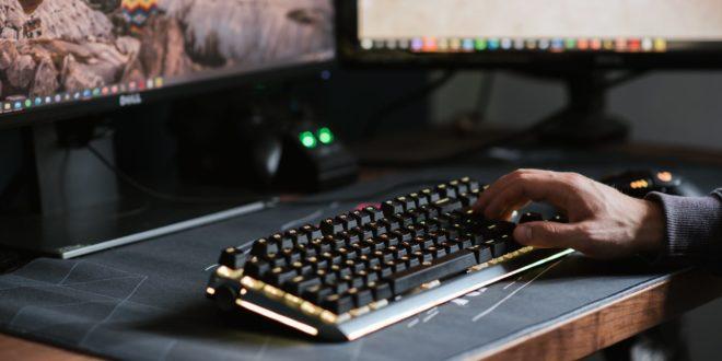 crop unrecognizable man typing on modern computer keyboard
