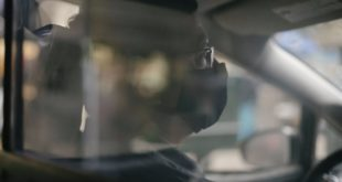 male taxi driver driving car in medical mask during coronavirus pandemic