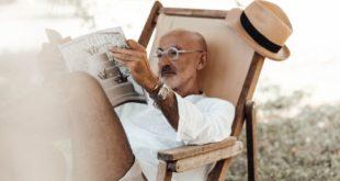 pensive ethnic man reading magazine in nature