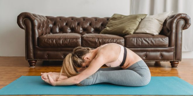 woman doing stretching on mat near leather sofa