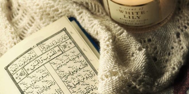 photo of quran beside lighted candle