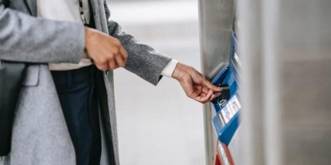 faceless woman buying metro ticket via electronic machine
